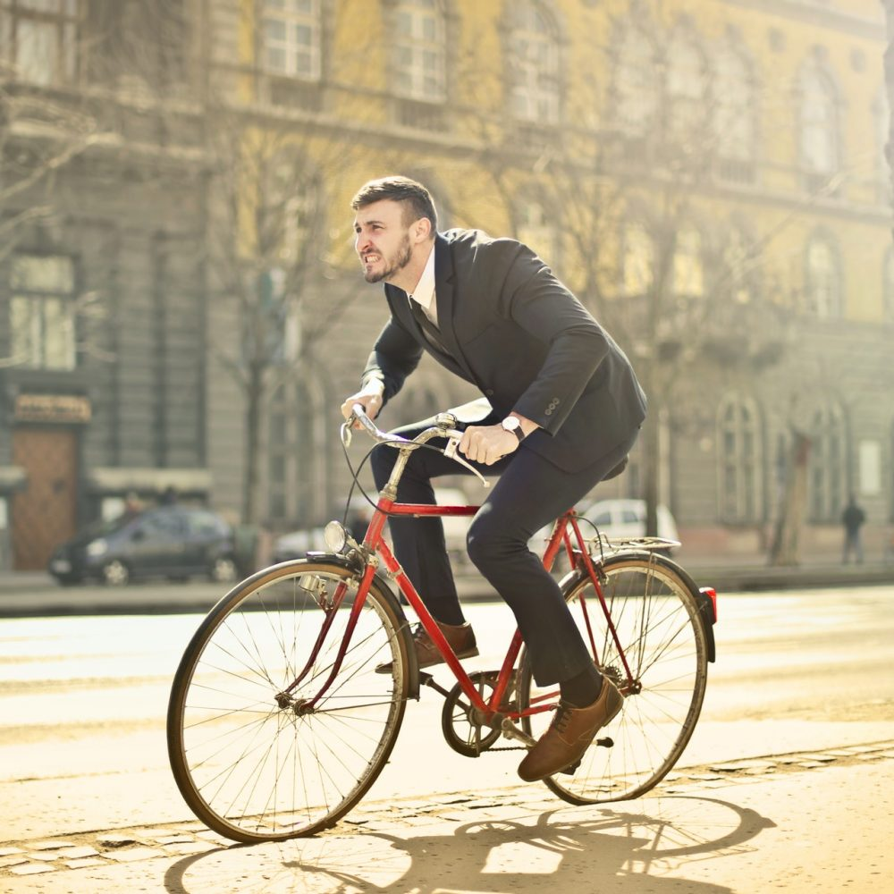 man-in-black-suit-riding-bicycle-down-the-street-1843752